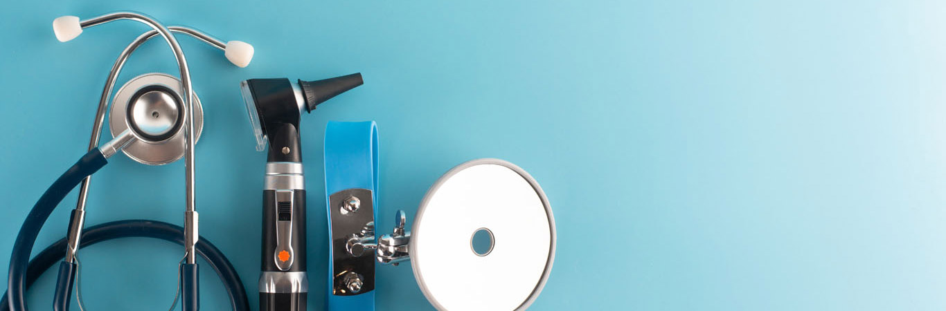 Otoscope with stethoscope and reflector mirror on blue background.